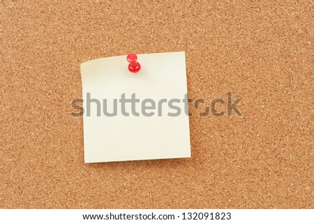 close up view of thumbtack and note on corkboard - stock photo
