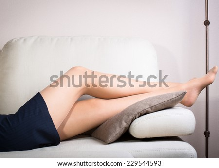 Close up view of tired woman foot on the sofa - stock photo