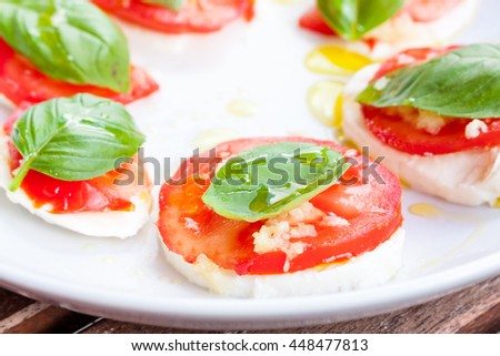 Close-up view of tomato, mozzarella and basil salad drizzled with olive oil on a white plate - stock photo