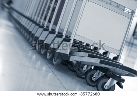 Close up view of trolleys  luggage in a raw in airport - stock photo