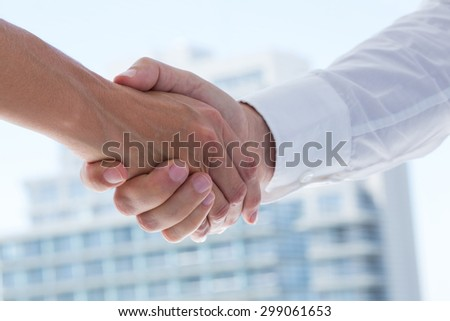 Close up view of two business people shaking hands in the office - stock photo