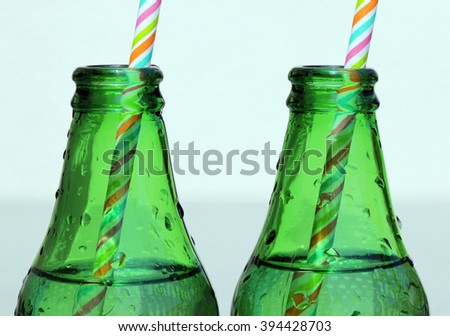 Close up view of two Glass Bottle of Water Necks with color striped straws at sunny summer day. - stock photo