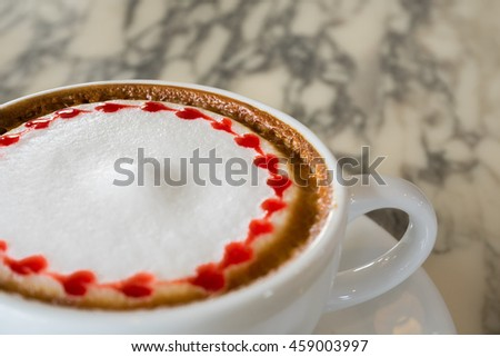 Close up view of white ceramic cup of hot cappuccino coffee with holder on the right side. The item is on light yellow marble table top with plate coaster - stock photo