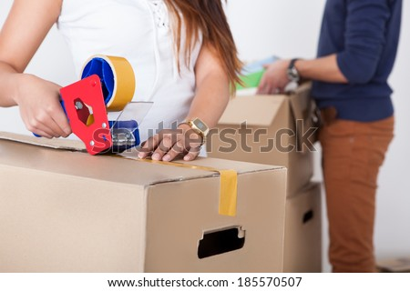 Close-up view of woman packing cardboard box with man standing in background at home - stock photo