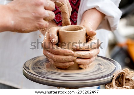 Close-up view of woman working on pottery wheel and making clay pot - stock photo