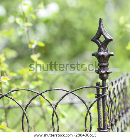 Close-up view of wrought-iron garden gate decoration with green grass and tree background, shallow DOF - stock photo