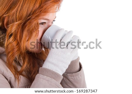 Close up view of young woman wearing winter clothes and drinking hot drink from a black cup, isolated on white background. - stock photo