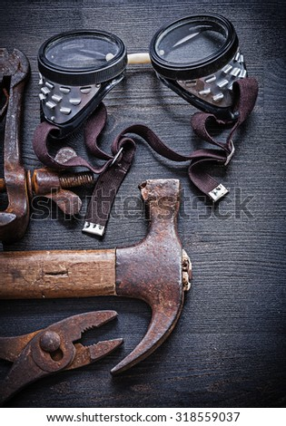 close up view on goggles hammer pliers on vintage wood board. - stock photo