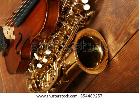 Close up view on musical instruments: saxophone, violin in wooden box - stock photo