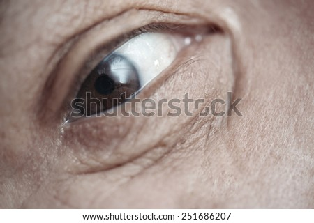 Close-up view on the eye of elderly human - stock photo
