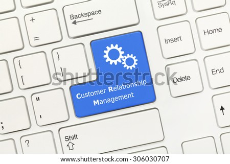 Close-up view on white conceptual keyboard - Customer Relationship Management (blue key) - stock photo
