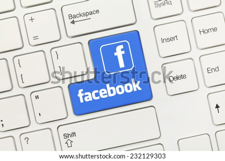 Close-up view on white conceptual keyboard - Facebook (blue key with logotype) - stock photo