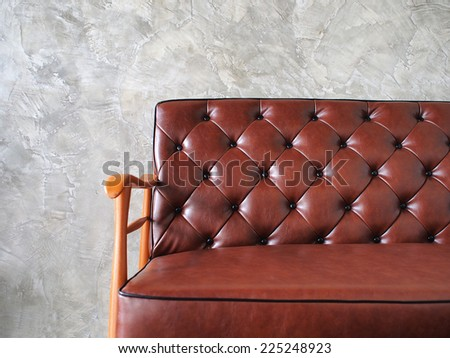 close up, vintage style of interior decoration the leather sofa and concrete wall - stock photo