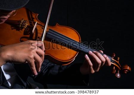 Close up Violin player in dark studio, Musical concept - stock photo