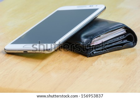 Close-up wallet and mobile phone on wood table - stock photo