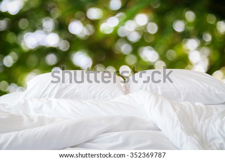 Close up white bedding sheets and pillow and abstract of blur light background - stock photo