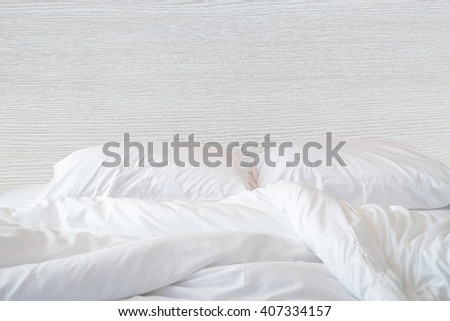 Close up white bedding sheets and pillow on wooden wall room background, Messy bed concept  - stock photo