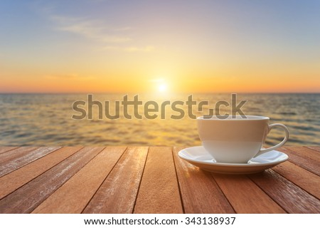 Close up white coffee cup on wood table and view of sunset or sunrise background  - stock photo