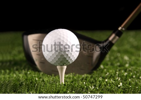 Close up white golf ball on white tee secured in green grass(artificial turf) with 1 wood driver (golf club) behind the ball ready to be hit, black background, space for copy to be added. - stock photo
