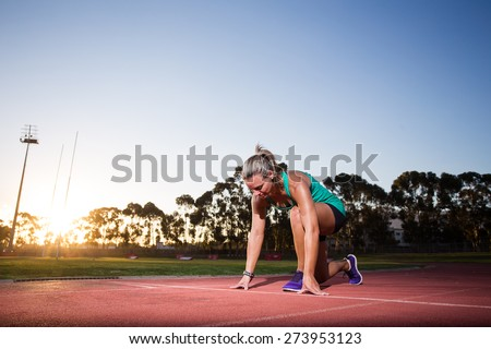 Close up wide angle view of a female sprinter  athlete getting ready to start a race on a tartan racetrack with dramatic lighting late in the afternoon, just before dusk. - stock photo