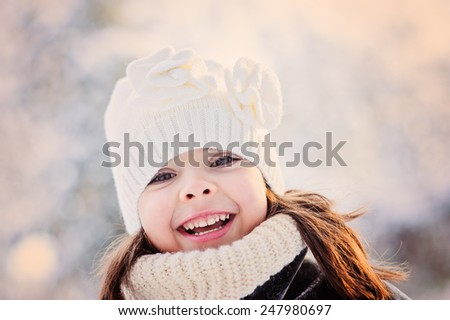 close up winter portrait of cute laughing child girl walking in sunny snowy forest  - stock photo