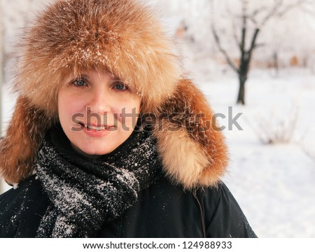 Close-up winter portrait of young smiling woman in fur hat - stock photo