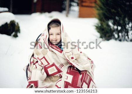 Close-up winter portret of  brunette kid girl with blue eyes in quilt comfort - stock photo