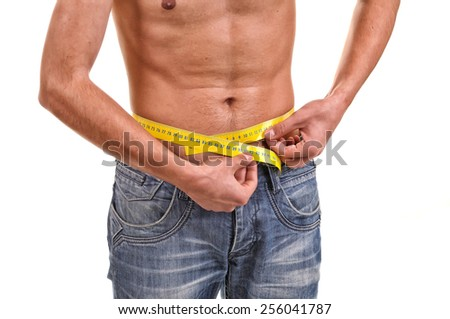 Close up with a waist and metter. Slim fit concept. Young fitness man measuring his waist - stock photo