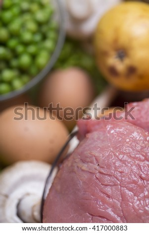 close-up with fresh meat, eggs, healthy vegetables, and washed fruit placed on a basket, selective focus - stock photo