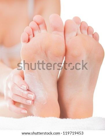 Close-up woman applying moisturizer cosmetic cream on foot on light background - stock photo