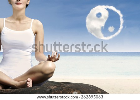 Close-up woman exercise yoga at beach with ying yang cloud - stock photo