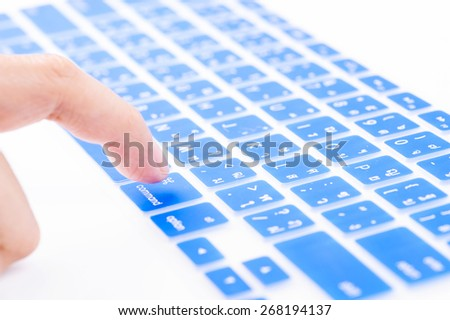 Close up woman finger on blue command button Thai keyboard cover - stock photo