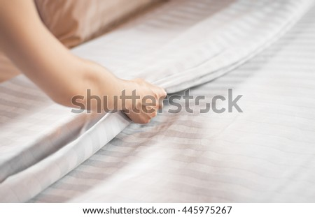 Close up woman hand set up white bed sheet in hotel room - stock photo