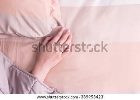Close up woman hand under blanket. - stock photo