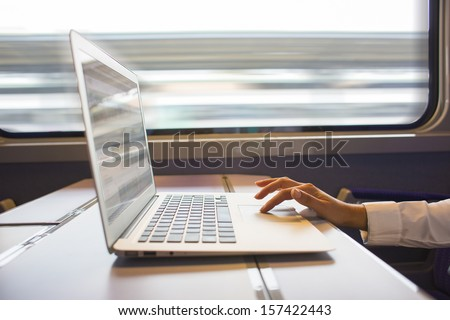 Close-up woman hands typing on a laptop keyboard, in the train  - stock photo