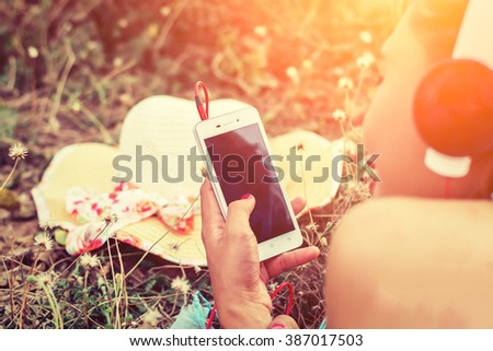 Close-up woman hands using smartphone to listening music laying and enjoying music in flower field - stock photo