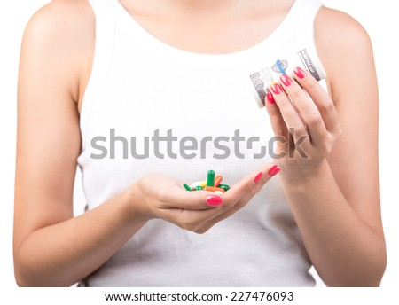 Close-up woman in white is taking the pills and money. Expensive drugs. - stock photo