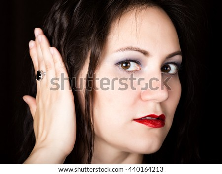 Close-up woman looks straight into the camera on a black background. laughing woman covers his ears with his hands. expresses different emotions - stock photo