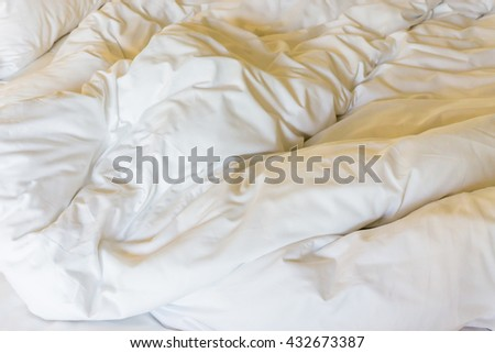 Close up wrinkle messy blanket on bed. Morning time. - stock photo