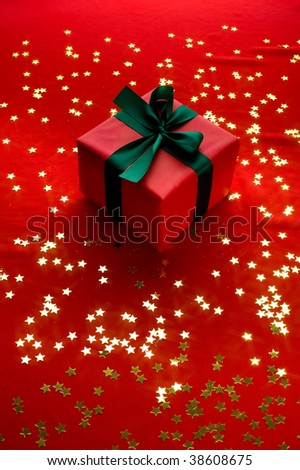 Close-up xmas gift over golden stars background - stock photo