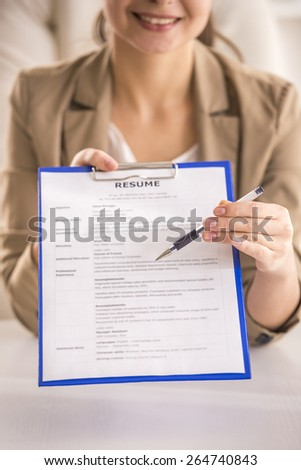 Close-up. Young beauty businesswoman showing on resume in office. - stock photo