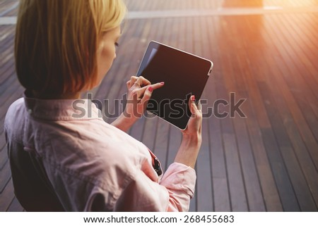 Close up young blonde female student using touch pad against wooden background, freelancer girl working on her digital tablet with big copy space, hipster woman browsing with touchscreen device, flare - stock photo