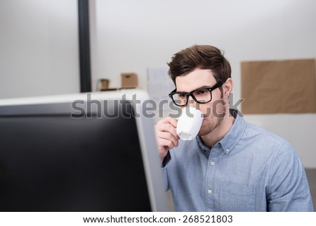 Close up Young Handsome Businessman Drinking Coffee in a Cup While Looking at the Computer Monitor on his Desk. - stock photo