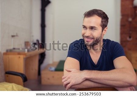 Close up Young Handsome Man Leaning on Chair, with Crossed Arms, Smiling on Right. - stock photo