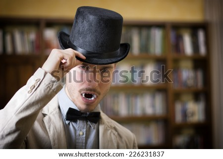 Close up Young Handsome White Vampire with Black Top Hat Inside the Mini Library - stock photo