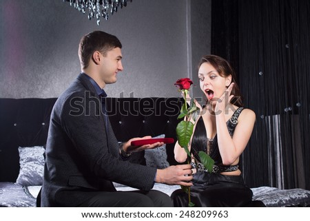 Close up Young Lady in Black Dress Received Jewelry and Red Rose Presents from her Boyfriend with Surprise Reaction. Captured at the Bedroom. - stock photo