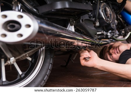 Close up Young Man Lying on the Floor While Fixing his Sports Motorbike Manually Using Wrench Hand Tool - stock photo