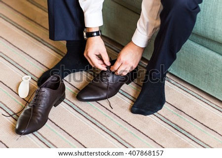 Close-up young man tying elegant shoes indoors - stock photo