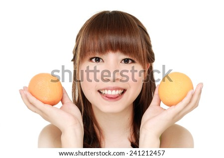 Close up young smiling woman showing orange  - stock photo