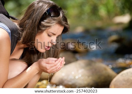 Close up young woman drinking fresh water from stream in nature - stock photo